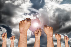 Human hand showing fist ready for fighting. Group of human hand showing fist on sky background with the sun, fighting fist concept, fist sign or symbol Royalty Free Stock Image