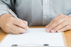 Human hand signing white paper on wood table Stock Photos