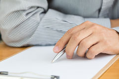 Human hand signing white paper on wood table Stock Image