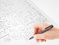 Human hand sketching ideas on a white paper Royalty Free Stock Photo