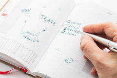 Human hand sketching multiple ideas on a organizer Stock Photos