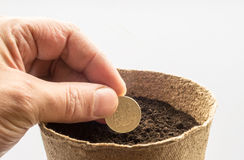 Human Hand Sowing a Pound Coin in Compost Royalty Free Stock Images