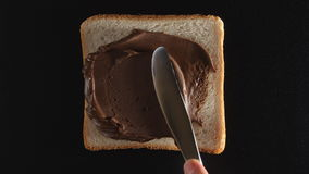 Human hand spreads a chocolate paste on a bread. Human hand spreads chocolate paste on a bread stock footage