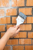 Human hand starting to paint brick wall Royalty Free Stock Photos