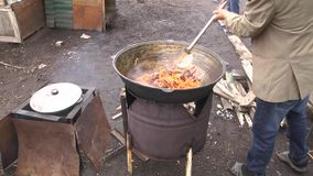 Human hand stir boiling oil with meat and spices with a wooden paddle, preparation of pilaf, front view stock video