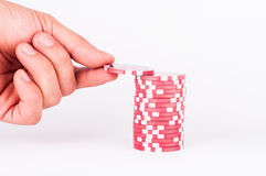 Human hand takeing red casino chips isolated on white Royalty Free Stock Photo