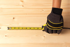 Human hand taking measurement on a block of wood. Worker taking measurement on a block of wood Royalty Free Stock Image