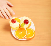 Human hand taking sweet gourmet cake. Gluttony. Royalty Free Stock Photography