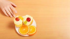 Human hand taking sweet gourmet cake. Gluttony. Royalty Free Stock Photos