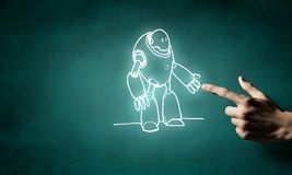 Funny sketched robot. Human hand touching with finger robot sketched design Stock Photo