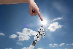 Human hand is touching robot hand against sky background Royalty Free Stock Image