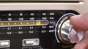 Human hand tuning a vintage radio