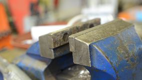 Human hand turning blue metal vice in workshop. Closeup stock footage
