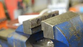 Human hand turning blue metal vice in workshop stock footage