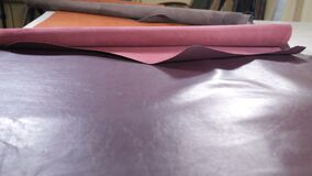 Human hand unrolling and touching leather roll. Rolls of industrial leather for clothing or accessories. In private