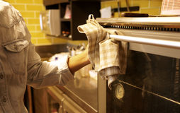 Human hand using hot oven with kitchen towel Stock Photography