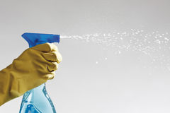 Human hand wearing rubber glove and holding spray bottle Stock Photos
