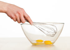 Human hand whisks eggs in glass blow Royalty Free Stock Photo