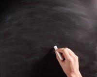 Human Hand Writing on an Empty Black Chalkboard Stock Image