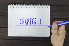 Hand writing on notepad: Chapter 1 stock image