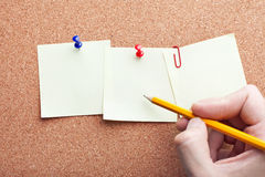 Human hand writing with pencil on note papers Royalty Free Stock Photo