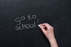 Human hand writing phrase go to school with piece Royalty Free Stock Photo