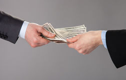 Human hands accepting an offer of money. On grey background royalty free stock photo