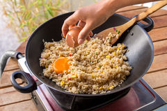 Human hands adding egg into fried rice royalty free stock photos