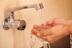Human hands being washed under stream of tap water Royalty Free Stock Images