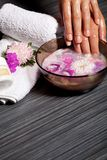 Human hands in bowl with oil and flower Royalty Free Stock Photo