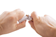Human hands breaking stack of cigarettes Stock Photo