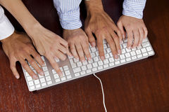 Human hands on computer keyboard, elevated view Stock Photos