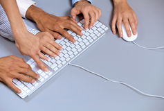 Human hands on computer keyboard with one hand using computer mouse Stock Photo
