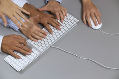 Human hands on computer keyboard with one hand using computer mouse Stock Photography