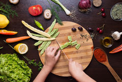 Human hands cutting green beans on a cutting board Stock Images