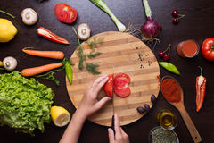 Human hands cutting tomato and vegetables and spices around. Photo from directly above of human hands cutting tomato and variation of different autumn vegetables Stock Photo
