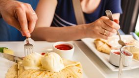 Eating pancake with ice cream and strawberry sauce. Human hands at dinner table holding fork and knife eating pancake with ice cream and strawberry sauce Royalty Free Stock Image