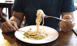 Human hands eating Asian rice noddle with folk and spoon Stock Photography