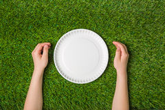 Human hands with empty plate on green grass Stock Photos