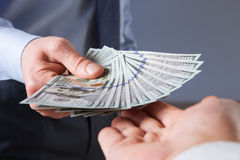 Human hands exchanging money on blue background. Closeup shot royalty free stock photography