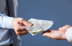 Human hands exchanging money on blue background. Closeup shot royalty free stock image