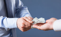 Human hands exchanging money on blue background royalty free stock image