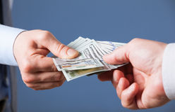 Human hands exchanging money. On blue background, closeup shot royalty free stock photography