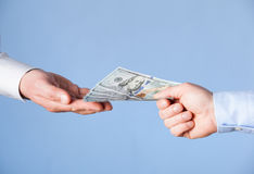 Human hands exchanging money. On blue background, closeup shot royalty free stock image