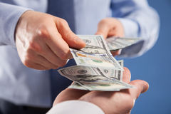 Human hands exchanging money on blue background Stock Image