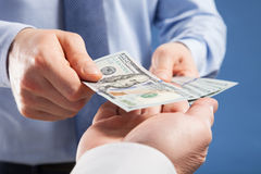 Human hands exchanging money on blue background Stock Photo