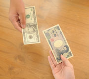 Human hands exchanging money. Japanese 1000 yen and 10 Dollar stock image