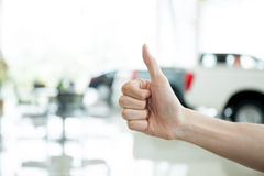 Human hands giving thumbs up with car key in car shoowroom Royalty Free Stock Photography