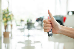 Human hands giving thumbs up with car key in car shoowroom Royalty Free Stock Image