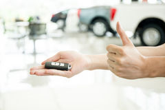 Human hands giving thumbs up with car key in car shoowroom Royalty Free Stock Photo